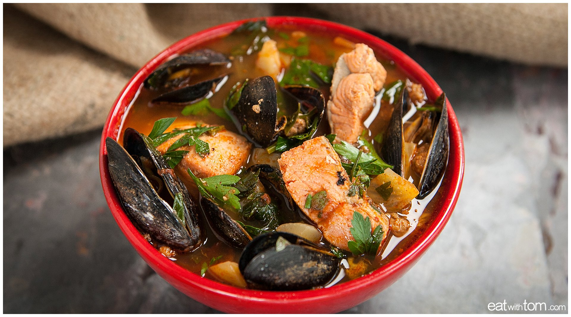Seafood stew recipe in red bowl with mussels salmon and cilantro - tom schmidt photographer